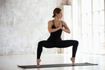 Hermosa mujer joven con ropa deportiva negra practicando yoga, de pie en pose de diosa en la estera, ejercicio de sentadilla de sumo, atractiva chica deportiva trabajando en el moderno estudio de yoga con grandes ventanales Foto de archivo