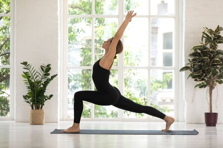 Young woman standing in Warrior one pose, practicing yoga, doing Virabhadrasana exercise, sporty girl wearing black sportswear working out at home or in yoga studio with big window and plants