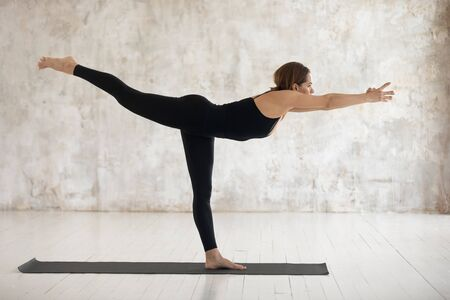 Beautiful young woman wearing black sportswear practicing yoga, standing in Warrior three pose, doing Virabhadrasana exercise, sporty girl working out at home or in yoga studio with grey walls 免版税图像