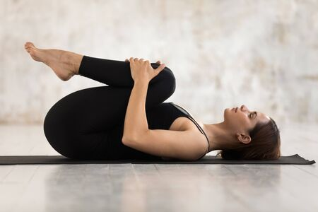 Beautiful young woman wearing black sportswear practicing yoga, relaxing in Knees to Chest pose, doing Apanasana exercise, sporty girl working out at home or in yoga studio with grey walls