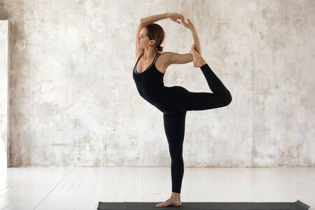 Beautiful young woman wearing black sportswear practicing yoga, doing Natarajasana exercise, standing in Lord of the Dance pose, sporty girl working out at home or in yoga studio with grey walls