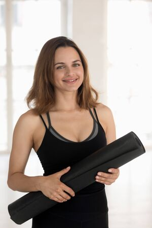 Head shot vertical portrait smiling woman wearing black sportswear holding yoga mat after or before working out, fitness coach, instructor looking at camera, sporty girl with fitness equipment Reklamní fotografie