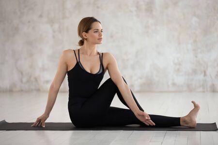 Belle jeune femme portant des vêtements de sport noirs pratiquant le yoga, assise dans la pose d'Ardha Matsyendrasana, faisant de l'exercice Half Lord of the Fishes, jolie fille travaillant à la maison ou dans un studio de yoga