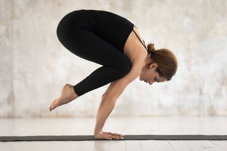 Attractive young woman wearing black sportswear practicing yoga, doing uttanasana exercise, standing forward bend pose, beautiful sporty girl working out at home or in yoga studio with grey walls 写真素材