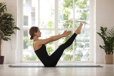 Beautiful young woman doing Paripurna Navasana exercise, boat pose, practicing yoga, attractive girl wearing black sportswear working out at home or in yoga studio with big window and plants