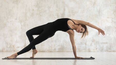Beautiful woman wearing black sportswear practicing yoga, standing in Wild Thing pose, attractive sporty girl doing Camatkarasana exercise, working out at home or in yoga studio, horizontal banner