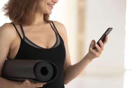 Smiling woman wearing sportswear, fitness instructor holding black yoga mat, sporty girl using phone close up, looking at screen, chatting in social network, break or waiting for training Stockfoto