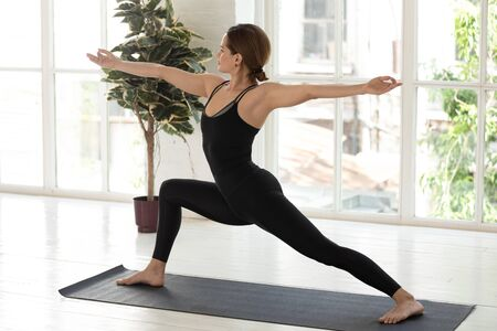 Beautiful woman wearing black sportswear practicing yoga, standing in Warrior Two pose, doing Virabhadrasana exercise, sporty girl working out at home or in yoga studio with big window and plants