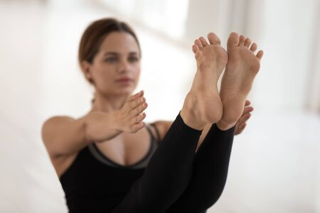 Beautiful young woman doing Paripurna Navasana exercise, boat pose, practicing yoga, feet close up, attractive sporty girl wearing black sportswear working out at home or in yoga studio Stockfoto