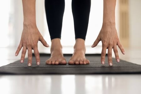 Young woman wearing black sportswear, pants practicing yoga, standing in uttanasana pose, doin Head to knees exercise, hands and feet on mat close up, girl working out at home or in yoga studio