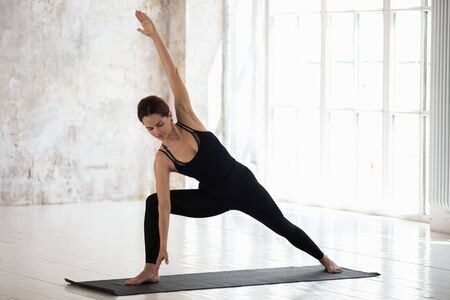 Young woman wearing black sportswear practicing yoga, standing in Utthita parsvakonasana pose, doing Extended Side Angle exercise, beautiful girl working out in modern yoga studio with big windows Stock fotó