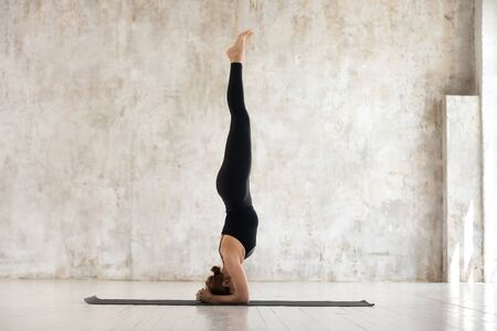Beautiful young woman wearing black sportswear practicing yoga, doing headstand exercise, standing in salamba sirsasana pose, sporty girl working out at home or in yoga studio with grey walls Foto de archivo