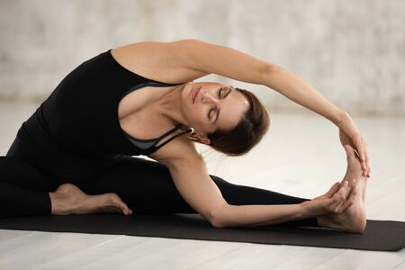 Young woman wearing black sportswear practicing yoga, doing Janu Sirsasana exercise, Revolved Head to Knee Forward Bend pose, girl working out at home or in yoga studio with grey walls close up