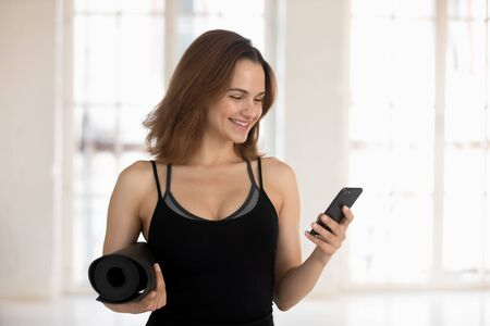 Smiling young woman, fitness instructor holding yoga mat, using phone, sporty girl looking at mobile device screen, chatting in social network, break or waiting for training Stockfoto