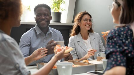 Happy african and caucasian business team people sharing pizza in office, friendly diverse multiracial staff employees talking laughing eating dinner food meal together having fun at corporate party