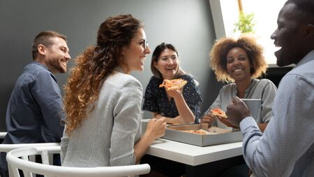 Cheerful multiracial business team people having fun eat pizza together, happy diverse company staff workers group chatting laughing in office share lunch food meal enjoy party at work sit at table