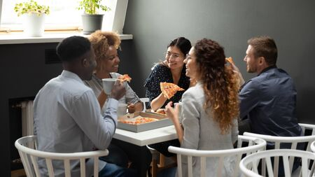 Happy multiethnic office business team people having fun share takeaway pizza together, diverse employees group laugh eat lunch dinner food meal talk enjoy corporate party meeting sit at work table Stock Photo