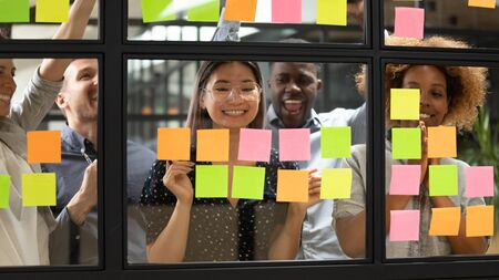 Happy asian female leader and multiethnic team celebrate corporate goal achievement, completed project success, finished task result, good teamwork growth stand behind glass wall with sticky notes Stock Photo