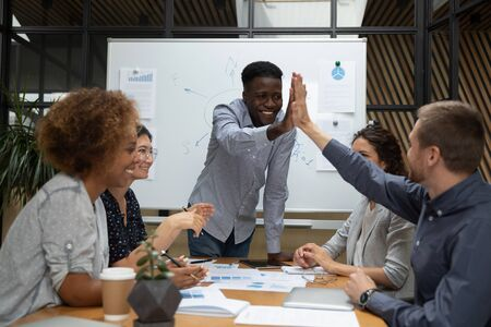 Happy diverse male designers team give high five at multiracial corporate group meeting satisfied with business agreement celebrate success victory good teamwork result thank for help in common work