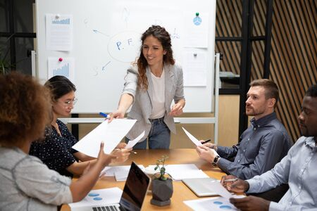 Smiling female company leader ceo give paper report business plan to diverse employees at group office meeting, businesswoman manager conducting team briefing work on paperwork at boardroom table