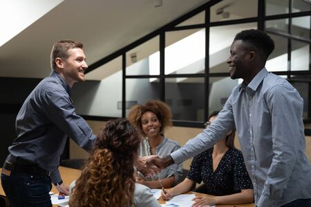 Smiling african and caucasian male business partners shake hands at group meeting at office table, happy diverse businessmen handshake express respect make deal establish partnership teamwork concept Stok Fotoğraf