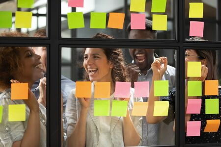 Overjoyed diverse business team people stand behind glass wall with sticky notes celebrate corporate success win victory, finished project job well done feel happy about good work results concept Stock Photo