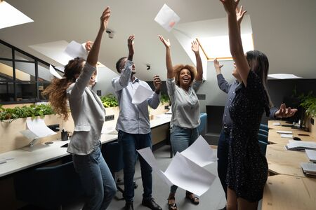 Happy overjoyed multiethnic business team people staff group throwing tossing papers up in office celebrate corporate success freedom at party enjoy victory dance having fun at workplace on friday
