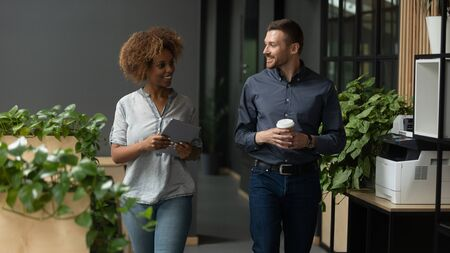 Two diverse professional colleagues talking walking in modern office, happy friendly african female and caucasian male coworkers having conversation discuss project going along business work space