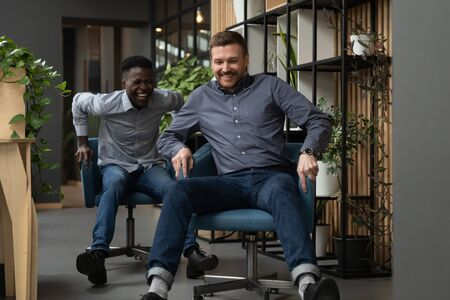 Two happy friendly diverse male colleagues laughing riding on chairs together in modern office, caucasian and african businessmen coworkers having fun enjoy friendship and funny corporate friday game