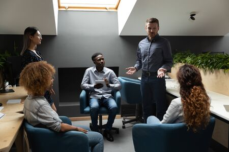 Confident caucasian male leader manager mentor explain project strategy talk to diverse employees work team at corporate group meeting, businessman executive ceo training teaching staff at workshop Stock Photo