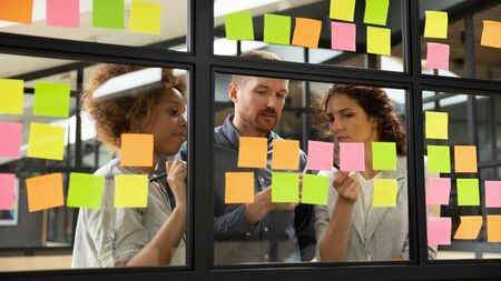 Diverse business team people share ideas brainstorm on corporate project strategy write ideas on post it sticky notes organize work process together look at glass scrum board at teamwork briefing