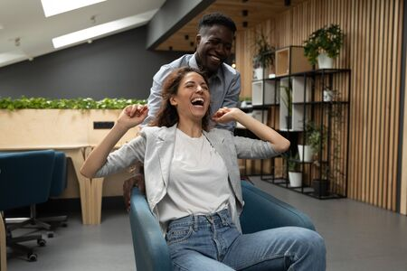 Cheerful happy diverse colleagues having fun riding on chair in modern office, caucasian female and african male team laughing celebrate corporate success victory enjoy funny friday activity together