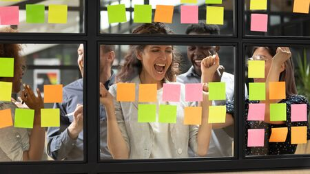 Ecstatic caucasian female leader and diverse business group celebrate success feel excited finishing corporate project achieved goal stand behind glass wall with sticky notes happy with team victory Stock Photo