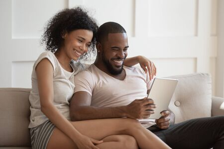 Smiling african american young woman cuddling happy husband, sitting on cozy sofa in living room at home, using tablet together, shopping or watching funny movies, photos, spending free weekend time.