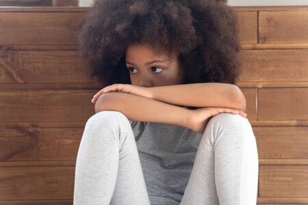 Close up cropped cute offended little african american girl sitting on floor, feeling lonely, suffering from misunderstanding, quarrel with parents or friends. Sad orphan being abused or bullied.