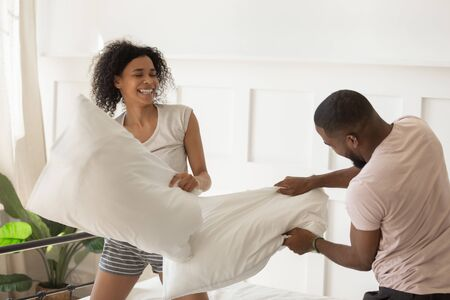 Overjoyed young family couple having fun with pillow fighting on bed after waking up in the morning in comfortable modern bedroom, happy african american spouse enjoying active weekend time at home.