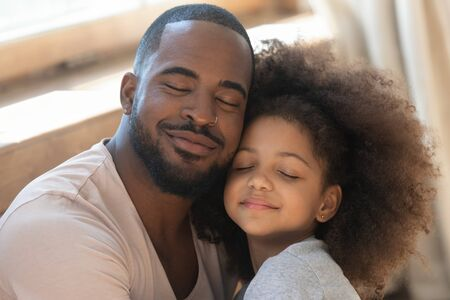 Close up head shot portrait young african american man embracing little cute curly preschool daughter, tender moment. Happy dad and little kid bonding hugging with closed eyes on fathers day. Фото со стока