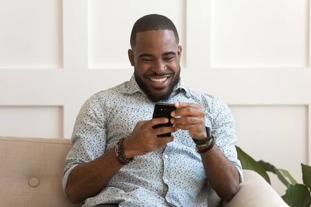Addicted happy smiling african american guy using mobile phone, watching funny videos, playing online game, chatting with friends, reading email with positive news, sitting on sofa at living room.