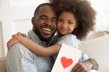 Excited happy african american dad holding cute little daughter and greeting card with red heart, tender Fathers Day celebration concept. Black preschool smiling girl hugging daddy, looking at camera.