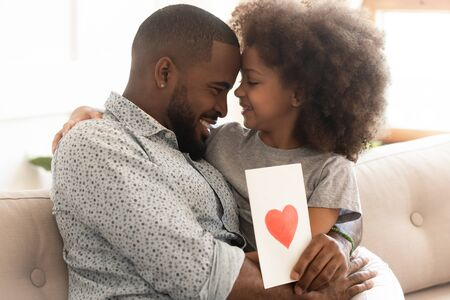 Thankful happy african american dad holding greeting card from little daughter. Cute smiling preschool girl sitting on daddys lap, embracing, celebrating Fathers Day, enjoying tender family moment. Reklamní fotografie