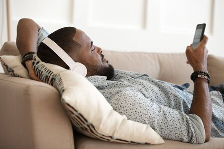Young handsome african american happy man lying on pillow on comfy sofa, relaxing, listening favorite music in modern wireless headphones, chatting in messenger, scrolling social networks.