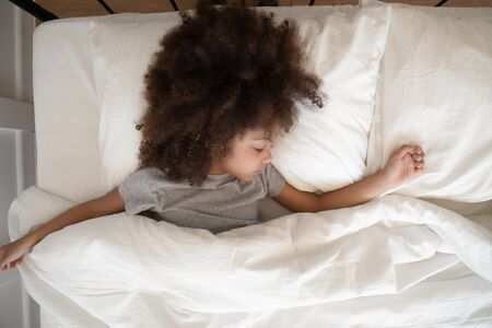 Top view adorable little curly african american kid girl sleeping alone under blanket in bedroom at home. Cute mixed race child daydreaming or watching sweet dreams, resting in comfortable hotel room.