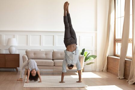Active happy african american girl doing bridge exercise, strong father staying on hands. Smiling black family doing morning exercises together in living room at home. Daily healthy habit concept.
