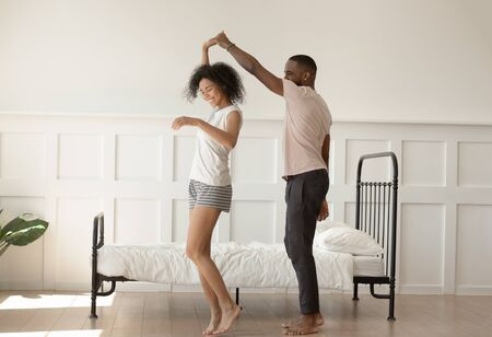 Happy barefoot african american loving family couple dancing in bedroom, enjoying honeymoon, romantic morning moment. Joyful guy twisting smiling wife, just married spouse in new apartment.
