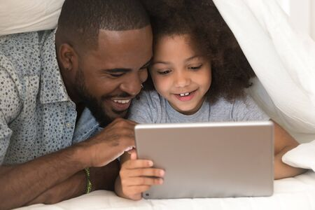 Happy african american father using digital tablet with cute small excited daughter, lying under blanket at home. Smiling black family playing online game, watching funny cartoon or shopping together. Stock fotó