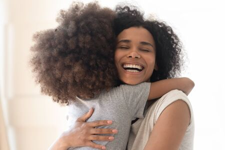 Happy excited single african american mother cuddling little preschool daughter close up headshot image. Overjoyed loving mixed race mom bonding, hugging, playing, having fun with cute kid girl. Reklamní fotografie