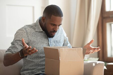 Shocked young african american male customer unpacking delivered cardboard parcel with order from internet online store, negatively surprised confused angry client received wrong or damaged item. Stockfoto