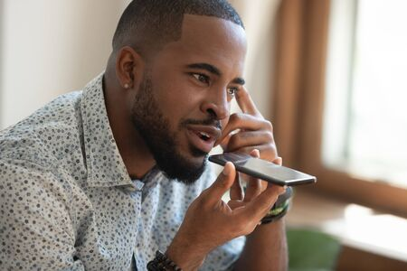 Close up thoughtful mindful african american guy sitting on couch, talking on speakerphone, dictating voice message, using online translator app or voice recognition software, virtual assistant. Archivio Fotografico