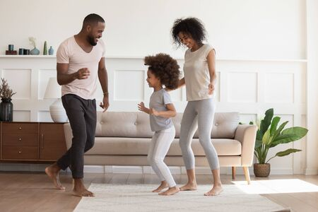 Happy african american family having fun, dancing at home. Smiling carefree cheerful black daddy, mommy and little kid daughter playing enjoying spending time together in modern living room.
