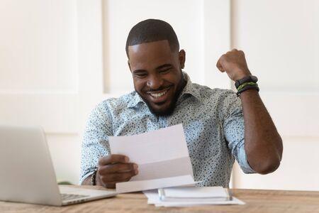 Heureux jeune afro-américain euphorique a reçu un rapport papier, une lettre d'admission à l'université, célébrant la réalisation d'objectifs importants, l'approbation de prêt bancaire, le remboursement intégral du crédit, l'avis de victoire à la loterie.